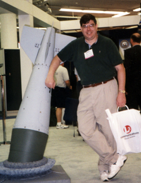 Larry Bond posing with an unexploded bomb before defusing it