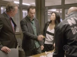 Jonny Lee Miller pointing out to Lucy Liu and Aidan Quinn they are one short of a battery