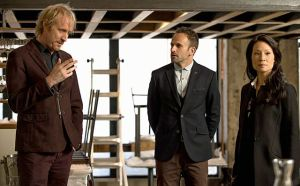 Mycroft (Rhys Ifans) shows Holmes (Jonny Lee Miller) and Watson (Lucy Liu) what's cooking